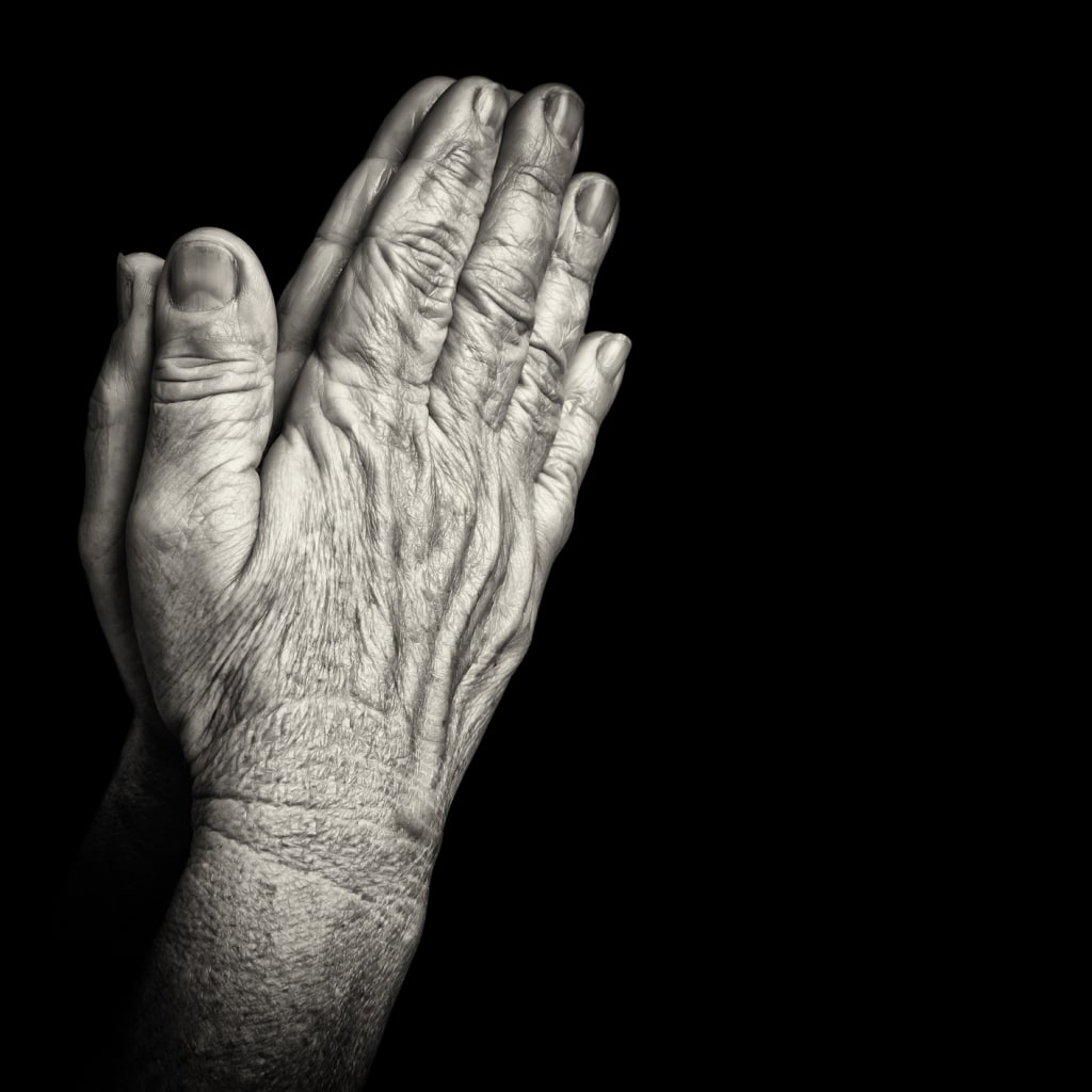 Old wrinkled hands praying